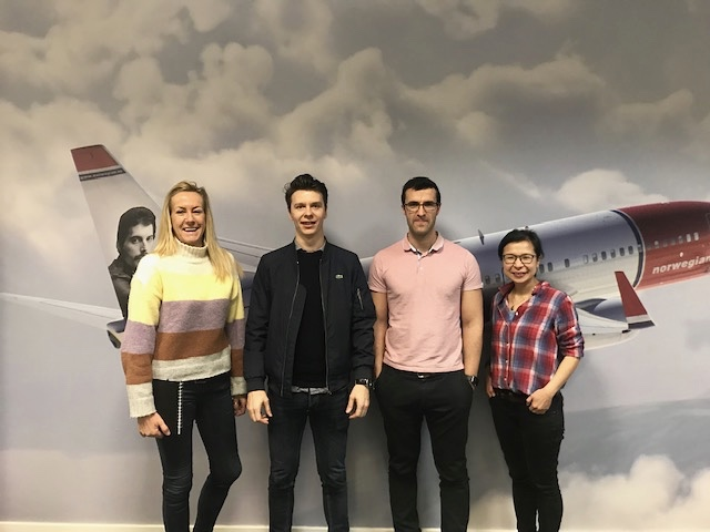 Four people in front of a wall post of a Norwegian airplane.