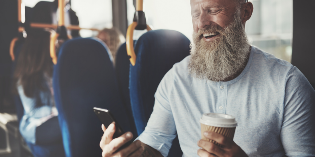 Man smiling while looking on phone, sitting on the train with his coffee